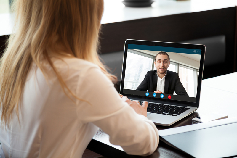 Woman on a business zoom video call with professional looking man