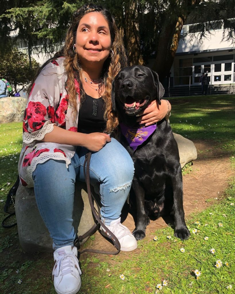 Daisy Soto with her guide dog sitting outdoors