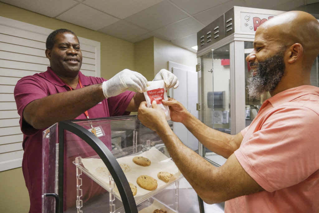 Employee who is blind handing over a cookie to a customer. Both people are smiling.