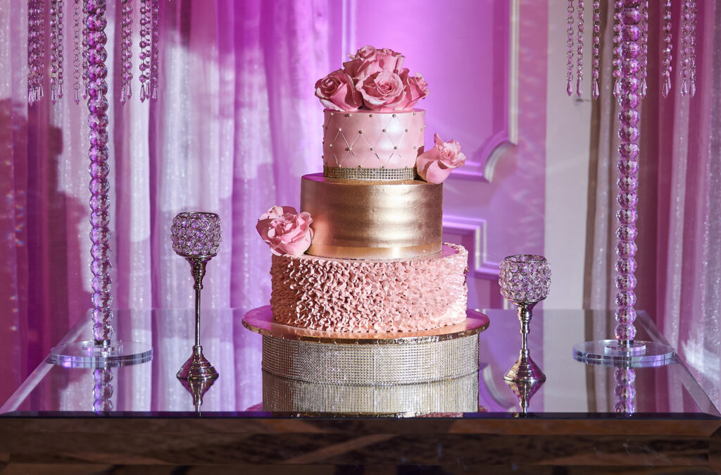Elegant quinceanera cake on a glass table surrounded by big flower arrangements.