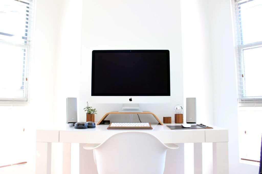 home office with view of desk and desktop monitor with accessories on the desk.