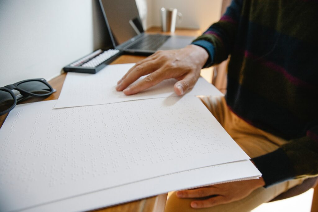 man reading reading a braille document sitting at a desk.