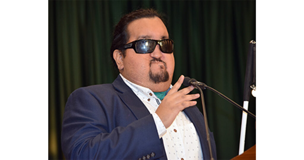 Photo of Daniel Martinez speaking at the microphone.