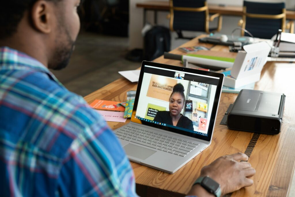 Man sitting at a table talks to a woman in a zoom meeting on a laptop.