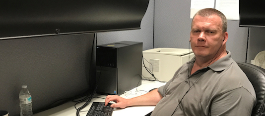 John Carty at desk on computer