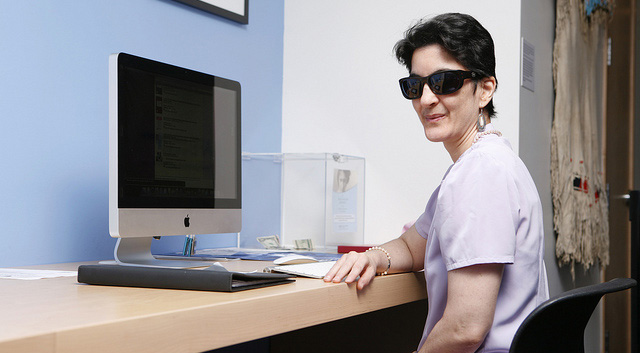 Woman wearing sunglasses and sitting at a computer.