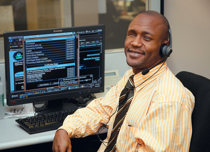 Blind man sitting at desk wearing a headset in a Call Center
