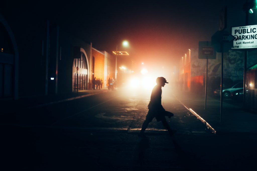 a dark street at night, a person walks by bright car headlights