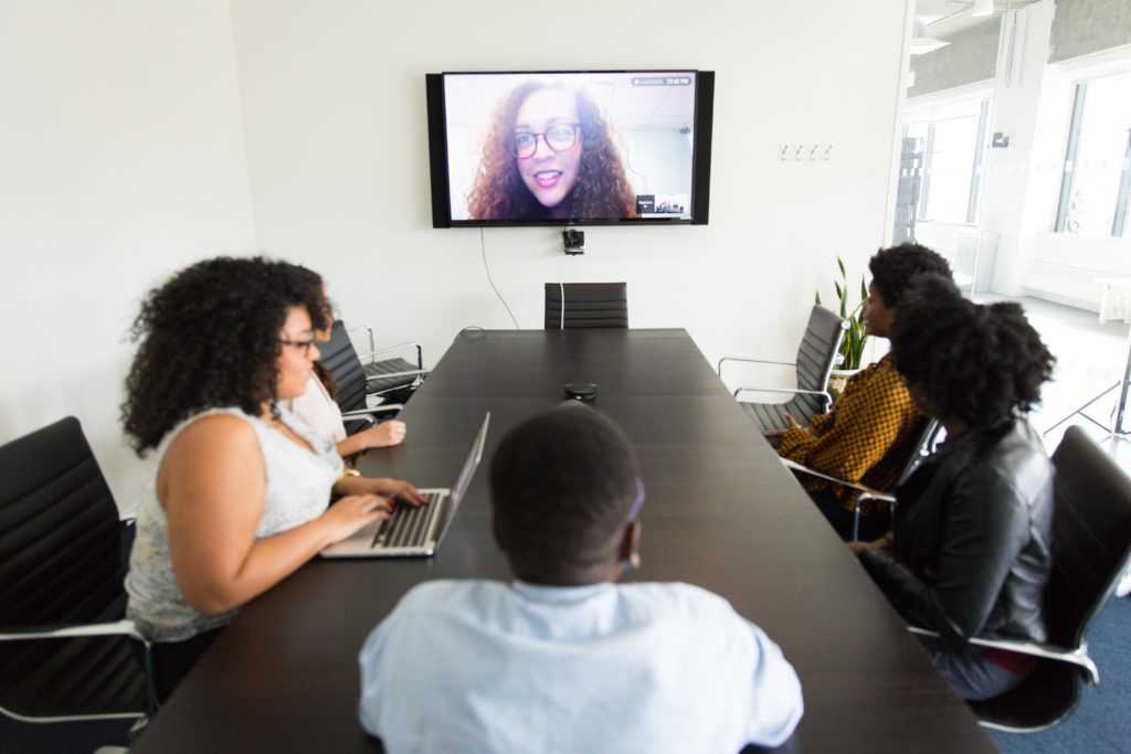 small group of people at a conference table and one person on a monitor