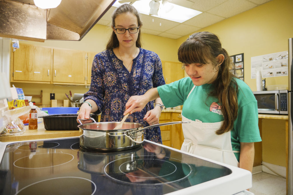 A teacher and student cooking in a classroom kitchen.