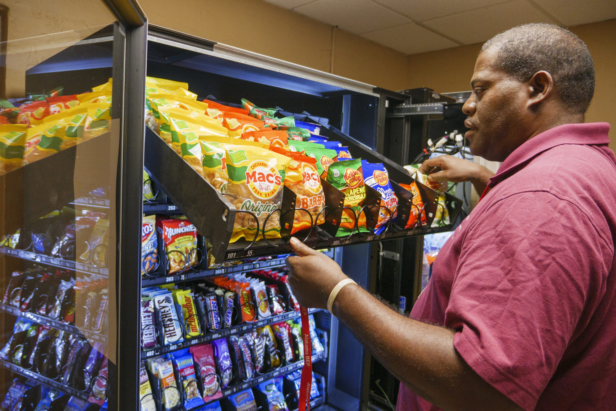 Man loading a vending machine with snacks.