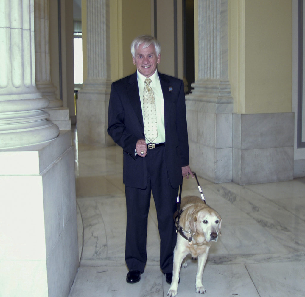 Man in suit and tie walking with a guide dog in a government building.