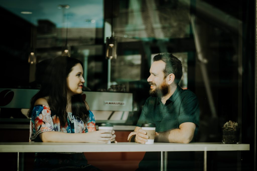 man and woman sitting at a table with hands around coffee mugs as if in a somewhat serious conversation.