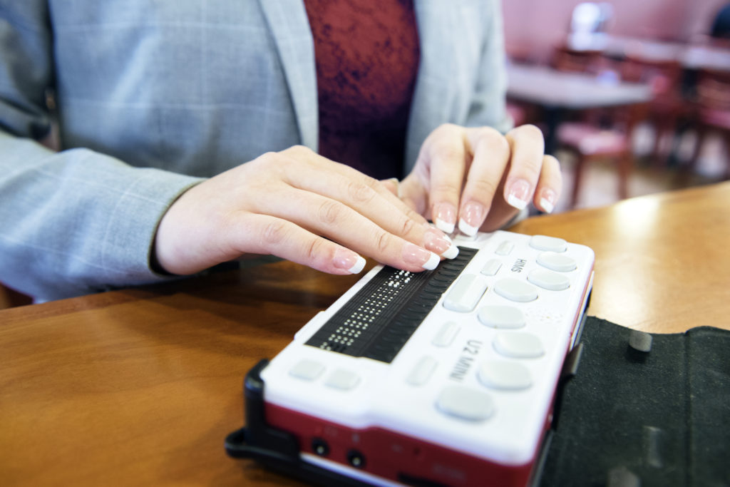 woman's hands reading a braille display