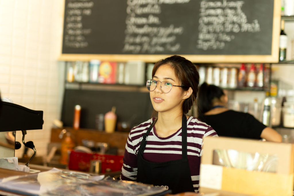 Teen girl wearing an apron behind the counter at a coffee shop