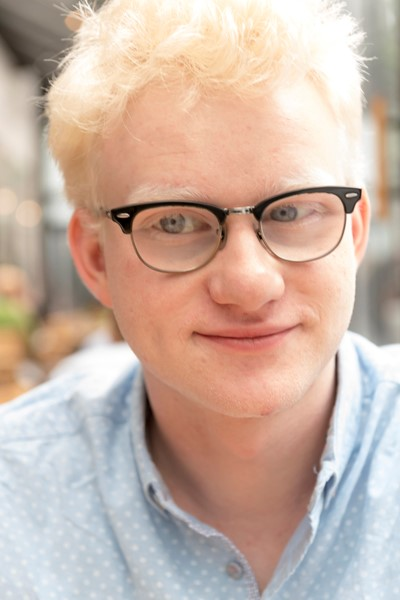 """Emmet Today"" - a young man with short blond hair, light blue eyes, and glasses sits facing the camera with a confident yet understated smile on his lips"