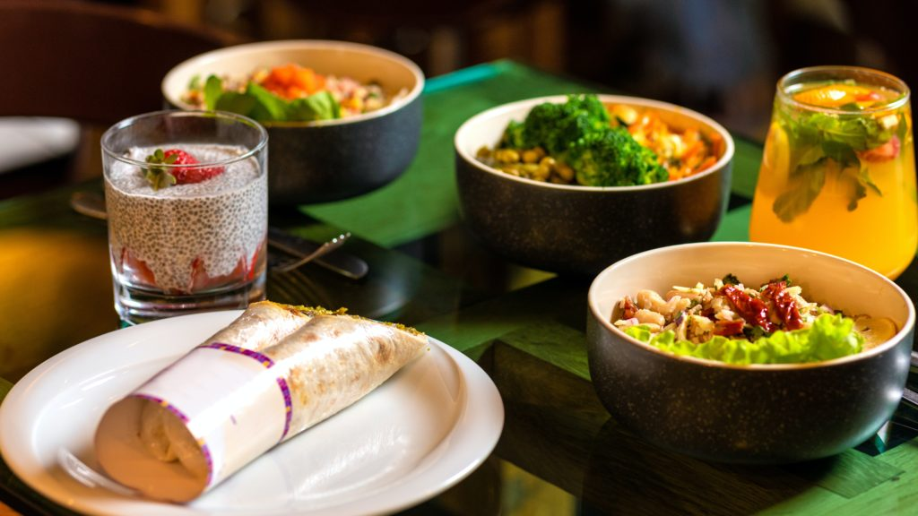 Dining table with food and drinks. # bowls filled with rice and vegetables